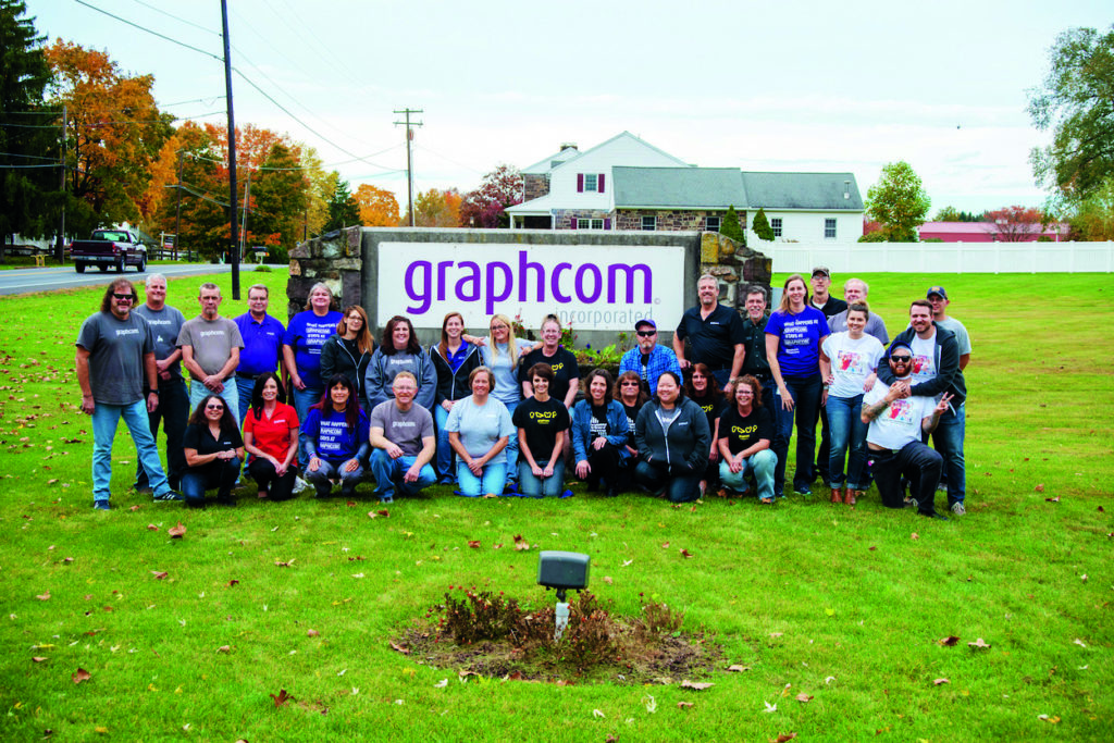 graphcom team photo in front of welcome sign